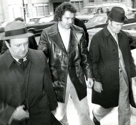 Frank Salemme brought into custody in 1972 by FBI agents for his role in orchestrating the bombing of a mob lawyer & future judge's car four years earlier